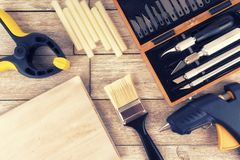Set of DIY tools on a white wooden plank, directly above. Glue gun, paint brush, clamp and precision knives stock images