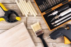 Set of DIY tools on a white wooden plank, directly above. Glue gun, paint brush, clamp and precision knives stock image