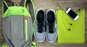 Set dla sportów butów, plecak, koszulka, telefon komórkowy z hełmofonu zakończeniem na drewnianym tle, odgórny widok Zdjęcia Royalty Free
