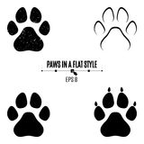 A set of dog`s paws. Black traces in different styles. Isolated on white background. Silhouettes of paws Stock Photography