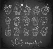 Set of doodle sketch cupcakes with decorations on blackboard background. Vector illustration. Stock Photos
