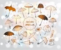 Set of doodle sketch umbrellas on white glowing background.  stock illustration