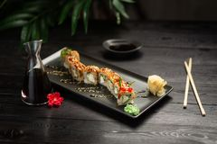 Set dragon rolls on a black plate on a black wooden background royalty free stock photo