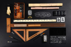 Set of drawing or draughtsman tools. Neatly arranged on grey with a ruler, callipers, paintbrushes, set square, right angle, stencil and ink Stock Photos