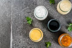Set of dressings for salad. Set of organic healthy dietary dressings for salad: sauce vinaigrette, mustard, mayonnaise with spices or ranch, balsamic or soy Royalty Free Stock Images