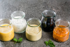 Set of dressings for salad. Set of organic healthy dietary dressings for salad: sauce vinaigrette, mustard, mayonnaise with spices or ranch, balsamic or soy Royalty Free Stock Photo