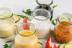 Set of dressings for salad. Sauce vinaigrette, mustard, mayonnaise or ranch, balsamic or soy, basil with yogurt. Dark white concrete table, with greenery Stock Images