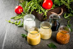 Set of dressings for salad. Sauce vinaigrette, mustard, mayonnaise or ranch, balsamic or soy, basil with yogurt. Dark stone table. On background of greenery Royalty Free Stock Photos