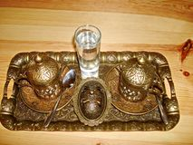 A set for drinking coffee, a cup and thrush, covered with bronze lids, made under the antiquity, top view of a close-up. stock photo
