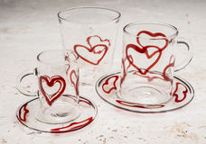 Set of Drinking Glassware with Red Hearts Design. A set of glassware including a small mug, a medium-sized mug on matching saucers, and a short tumbler, all with Stock Photos
