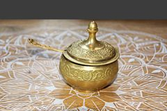 A set for drinking tea, a cup and thrush, covered with bronze lids, close-up view. stock photo
