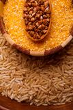 Set of dry cereals. Buckwheat, rice, wheat in a large brown plate. In a large brown plate with rice there is a small wooden plate with yellow wheat grains on stock photos