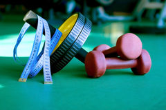 Set of dumbbels, exercise wheel and tape measuring. In gym Royalty Free Stock Photos