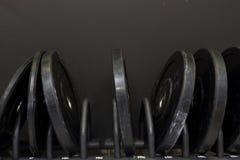 Set duzi metali ciężary na stojaku w gym z zmrokiem popielatym, czarny tło zdjęcie royalty free