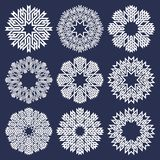 Set of eight pointed circular patterns in Oriental intersecting lines style. Nine white mandalas in snowflakes form. On blue background vector illustration