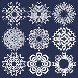 Set of eight pointed circular patterns in Oriental intersecting lines style. Nine white mandalas in snowflakes form. On blue background stock illustration