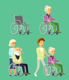 Set of elderly people in wheelchair. Social worker strolling with senior woman in wheelchair. Mature lady shows something her disabled companion Royalty Free Stock Image