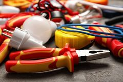 Set of electrician`s tools. On gray table stock photography