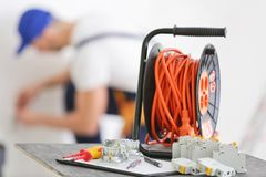 Set of electrician tools and blurred man at work. On background Royalty Free Stock Photography