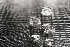 Set of Empty little bottles with black leather background Stock Photos
