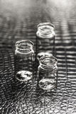 Set of Empty little bottles with black leather background Royalty Free Stock Photos