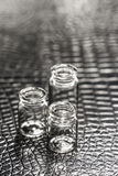 Set of Empty little bottles with black leather background Royalty Free Stock Images