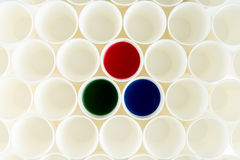 Set of empty plastic cups and cups with red, green and blue paints Stock Images
