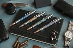 Pen set luxury. A set of expensive collectible pens made of wood. Raskladka accessories, glasses, watches, knives, compass, note book, wooden background Royalty Free Stock Photo