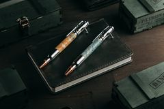 Set of expensive military pens in wooden boxes. Compositions on a dark background with attributes Royalty Free Stock Photo