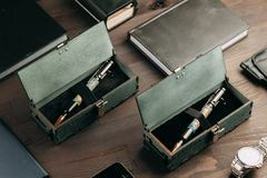 Set of expensive military pens in wooden boxes. Compositions on a dark background with attributes royalty free stock image