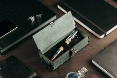 Set of expensive military pens in wooden boxes. Compositions on a dark background with attributes Royalty Free Stock Images