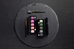 Set of eye shadows palettes with brushes on round stock photos