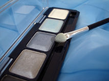 Set of eyeshadows and applicator brush on blue Stock Image