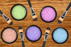Set of 5 eyeshadows and brushes over wooden texture close-up Royalty Free Stock Images