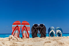 Set of family sandals on the sandy beach, vacation concept. Set of family sandals on the sandy beach with blue sky as a background, vacation concept stock photo