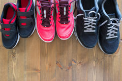 Set family shoe on the floor. Three pairs of athletic shoes on the floor Stock Images