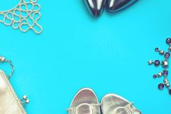 Set of fashion accessories flat lay shoes handbag necklace jewelry silver color on blue background Top view copy space. Set of fashion accessories flat lay shoes royalty free stock photo