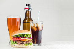 Cola, beer and burger. Set of fast food from cola, beer glass and burger on a white table royalty free stock images
