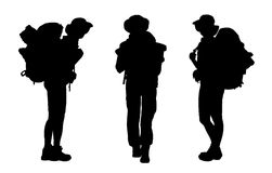 Set of female backpacker silhouettes. 3 black silhouettes of female backpackers waking and standing, carrying big tourist bags Royalty Free Illustration