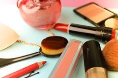 Set of female cosmetics from lipstick, highlighter, lip liner, brushes, brushes, perfume, powder, jewelry on a blue background. Beauty box Flat lay. Top view royalty free stock photography