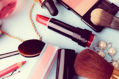 Set of female cosmetics from lipstick, highlighter, lip liner, brushes, brushes, perfume, powder, jewelry on a blue background stock photos
