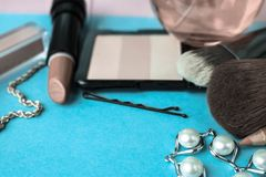 Set of female cosmetics from lipstick, highlighter, lip liner, brushes, brushes, perfume, powder, jewelry on a blue background royalty free stock photo