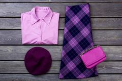 Set of female elegant attire. Women purple color shirt and skirt, wooden background. Feminine fashion clutch and beret. Ladies classy apparel flat lay Royalty Free Stock Photo