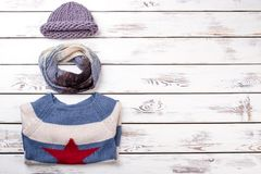 Set of female winter apparel. Women hat, scarf and sweater on wooden background, copy space. Female casual outfit Stock Photo