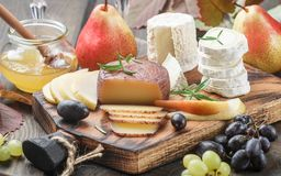 Set of fine cheeses with fruit and honey Royalty Free Stock Photography