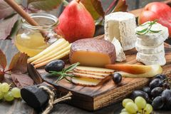 Set of fine cheeses with fruit and honey Royalty Free Stock Photos