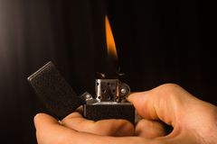 Set on fire with zippo. The male hands are setting fire up in zippo for smoking on black background Royalty Free Stock Image