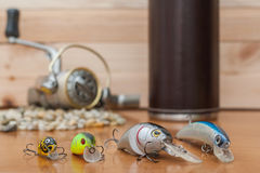 Set a fisherman on a wooden background. Baits unknown manufacturers in the foreground, a thermos with a coil in the background. 05. Set a fisherman on a wooden Stock Photo