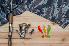 Set for fishing on the wooden background with camouflage clothing. Coil, colored rubber bait, spinning, fishing rod. Stock Image