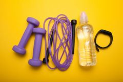 Set for fitness on a yellow background: skipping rope, dumbbells, fitness bracelet and water in a bottle royalty free stock images
